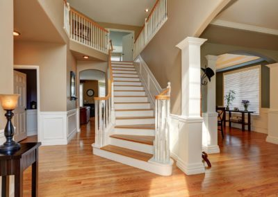 Sunny hallway interior with a staircase and hardwood floor.